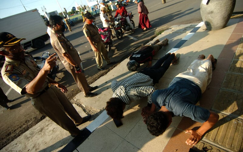 Anggota Satpol PP memberikan hukuman kepada warga