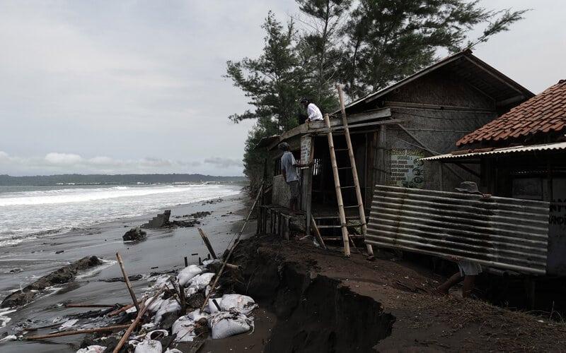 Sejumlah warga membongkar bangunan yang terancam abrasi akibat hantaman gelombang tinggi di Pantai Tegalkamulyan, Cilacap, Jawa Tengah, Rabu (27/5/2020). - Antara/Idhad Zakaria