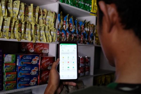 Seorang pemilik warung menggunakan aplikasi Mitra Tokopedia - Tokopedia