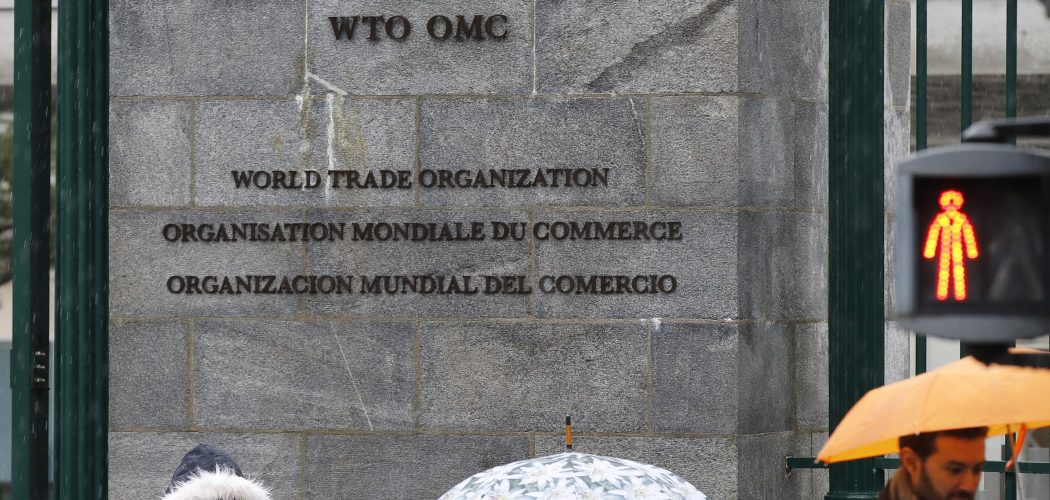 Pejalan kaki berjalan di depan kantor pusat World Trade Organization (WTO) di Jenewa, Swiss (Senin (2/3/2020). - Bloomberg/Stefan Wermuth