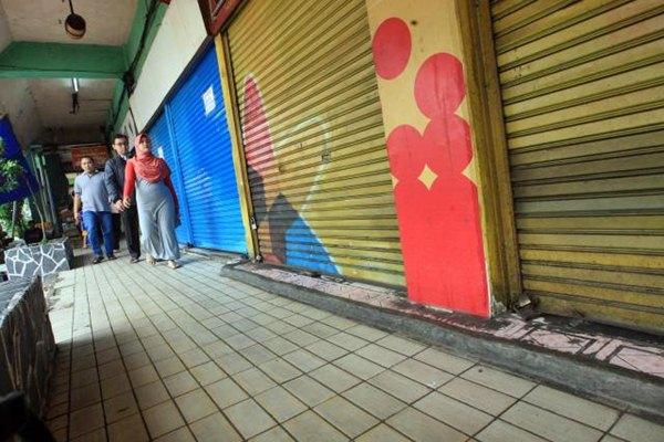 Pengunjung berjalan melewati toko yang tutup sementara di Pasar Slipi Jaya, Jakarta,Rabu (19/4). - JIBI/Dedi Gunawan