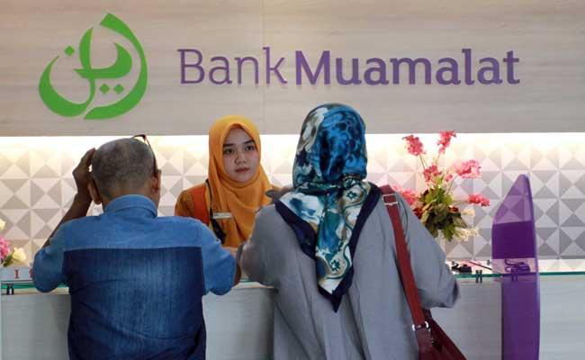 Karyawan melayani nasabah di Bank Muamalat Cabang Makassar, Sulawesi Selatan. Bisnis - Paulus Tandi Bone