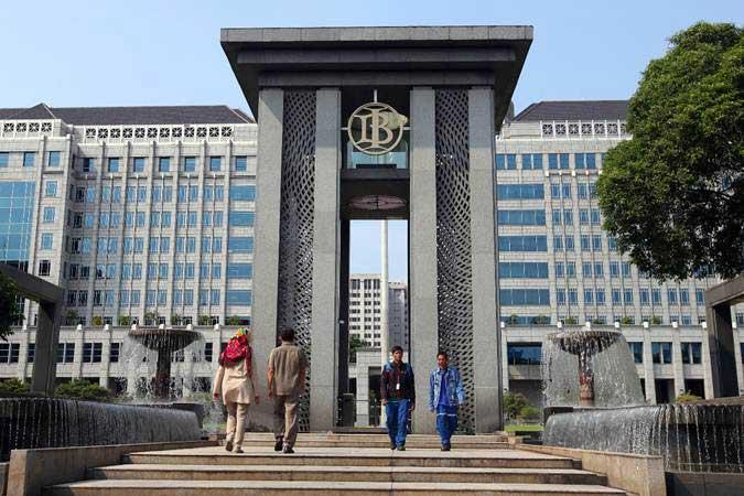 Ilustrasi - Karyawan melintas di dekat logo Bank Indonesia (BI) di Jakarta - Bisnis/Abdullah Azzam