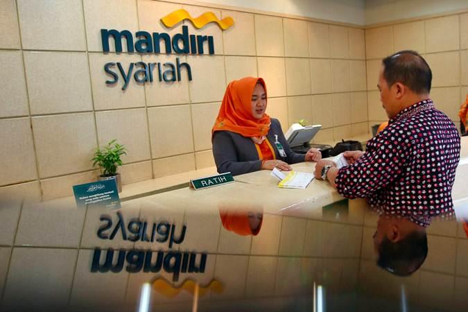 Karyawan melayani nasabah saat transaksi di Kantor Cabang Mandiri Syariah Thamrin, Jakarta, Senin (25/2/2019). - Bisnis/Abdullah Azzam