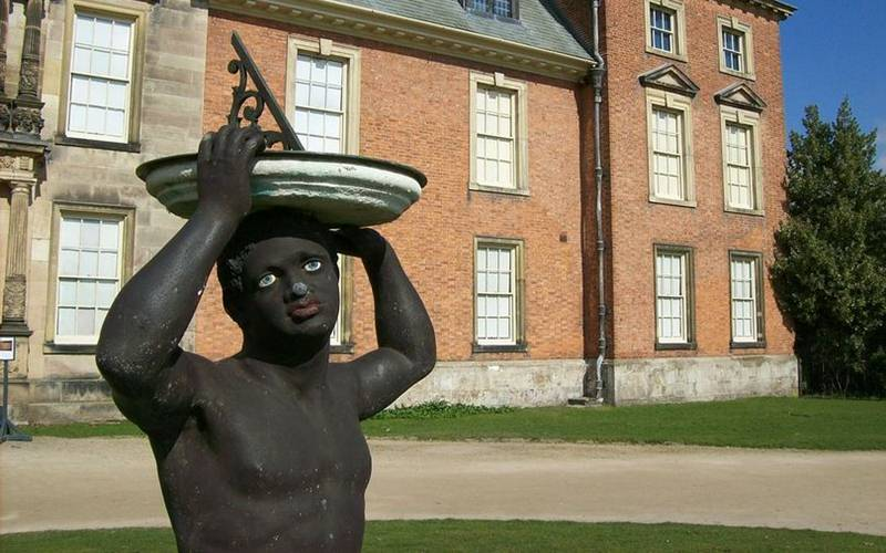 Patung pria berkulit hitam dengan jam matahari di kepala di depan halaman Dunham Massey. - manchestereveningnews.co.uk/Wikimedia Commons