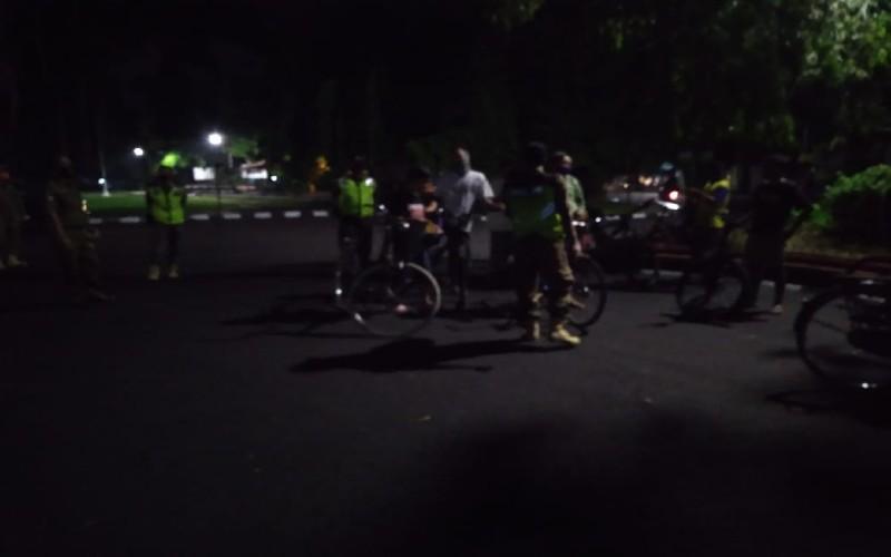 Petugas membubarkan kerumunan pegowes di Utara Lapangan Denggung, Sleman pada Sabtu (13/6 - 2020) malam. Foto: Istimewa