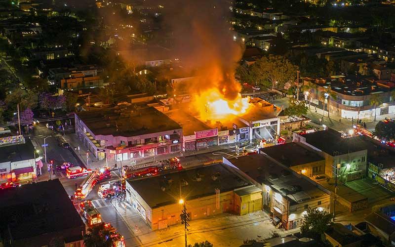 Sebuah bangunan terbakar saat aksi protes atas kematian George Flyod di Los Angles, California, Amerika Serikat, Sabtu (30/5 - 2020). Bloomberg