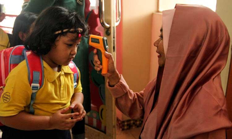 Petugas sekolah memeriksa suhu tubuh siswa menggunakan termometer non kontak saat sosialisasi di Sekolah Tunas Global, Depok, Jawa Barat, Selasa (3/3/2020). Kegiatan tersebut sebagai upaya antisipasi Virus Corona pada usia dini dengan mengukur suhu tubuh saat memasuki sekolah dan mensosialisasi penggunaan masker yang benar saat sakit. ANTARA FOTO - Asprilla Dwi Adha