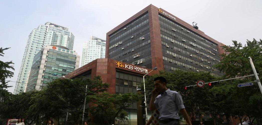 Pejalan kaki melintas di depan kantor Kookmin Bank di Korea Selatan - Bloomberg