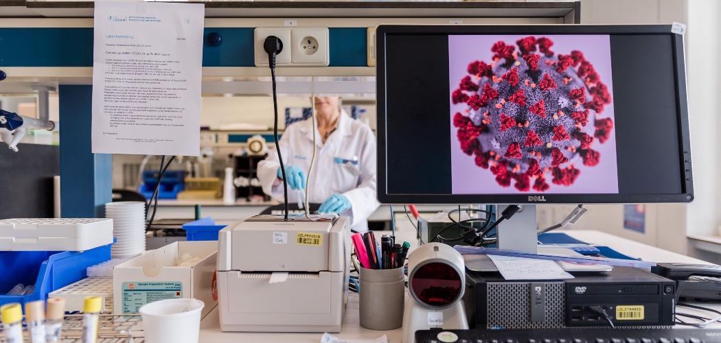 Tampilan virus corona yang diperbesar terlihat di monitor sebuah komputer di laboratorium penelitian virus di Rumah Sakit Universitas UZ Leuven, Leuven, Belgia, Jumat (28/2/2020). - Bloomberg/Geert Vanden Wijngaert