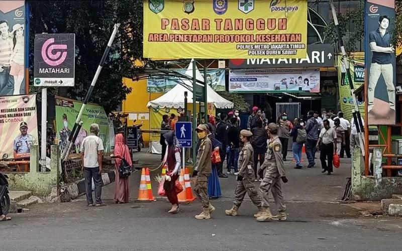 Petugas Satpol PP melintas di depan pintu masuk Pasar Perumnas Klender, Jakarta Timur, pada hari pertama penerapan mekanisme ganjil genap kios pedagang, Senin (15/6/2020). - Antara