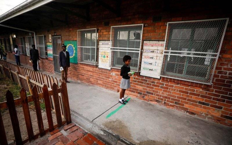 Murid-murid berdiri pada tanda jarak fisik saat mengantre makanan sekolah di Gugulethu di Cape Town, Afrika Selatan, 24/4/2020, di tengah pemberlakuan karantina secara nasional untuk mencegah penyebaran penularan virus corona (Covid-19)/Antara/Reuters/Mike Hutchings - TM