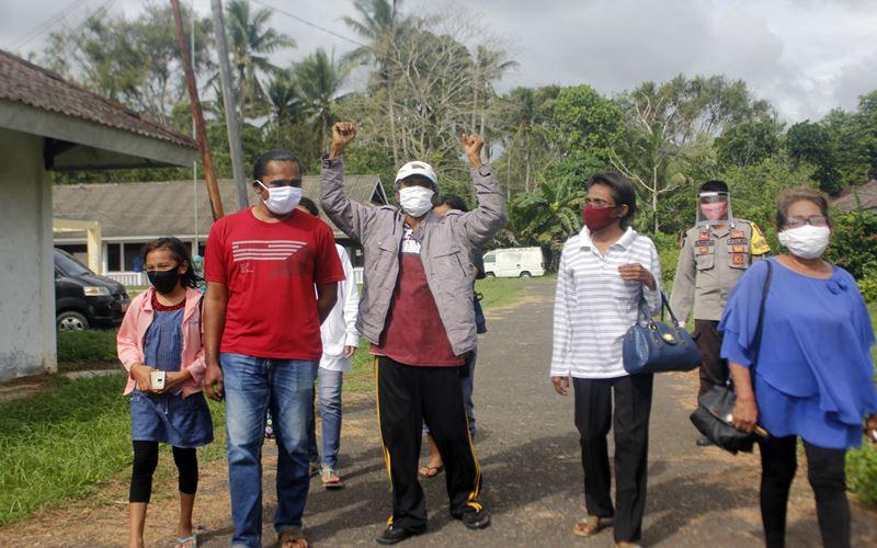 Pasien Positif Covid-19, Yohanes Tentua berusia 71 tahun (ketiga kiri) mengangkat tangan sebagai ucapan syukur usai dikarantina selama 14 hari di Balai Diklat Kampung Salak, Kota Sorong, Papua Barat, Senin (11/5/2020). Yohanes merupakan salah satu pasien positif Covid-19 dengan riwayat penyakit bawaan Tuberculosis (TBC) yang dinyatakan negatif usai perawatan dan karantina selama 14 hari di Balai Diklat Kota Sorong bersama keluarganya. ANTARA FOTO - Olha Mulalinda