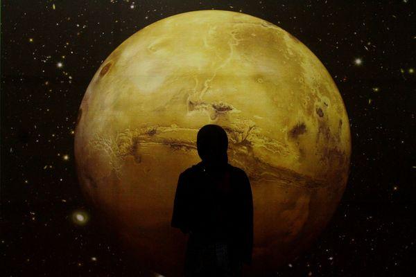 Peserta melintas di depan gambar bulan dalam fase merah atau