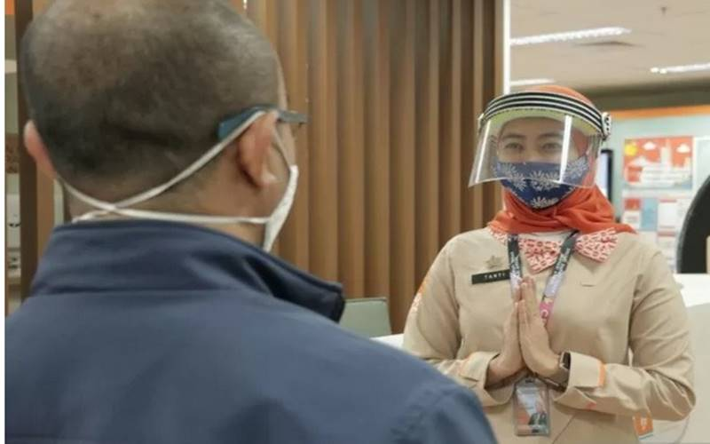 Petugas di Mal Pelayanan Publik DKI Jakarta menyambut masyarakat di hari kedua pembukaan dalam PSBB Transisi, Selasa (16/6/2020). - Antara\n\n