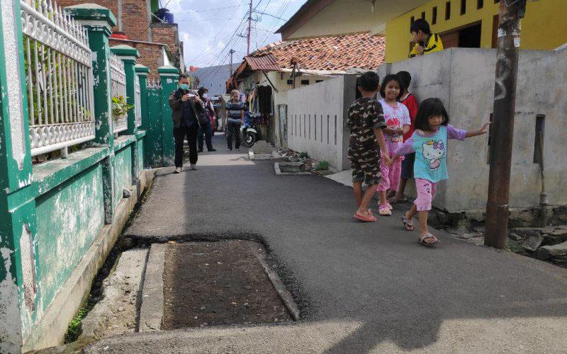 Warga melintas di dekat makam yang berada di jalan umum kawasan Pisangan Lama, Jakarta Timur, Selasa 16 Juni 2020. Warga setempat menyebutkan makam keluarga itu ada sejak 1940. - Antara/Kantor Kelurahan Pisangan Timur