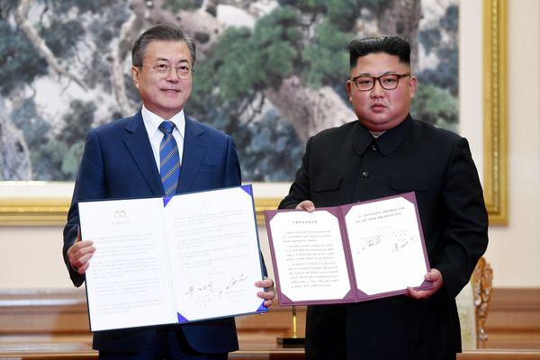 Presiden Korea Selatan Moon Jae-in dan pemimpin tertinggi Korea Utara Kim Jong Un menunjukkan pernyataan bersama kedua negara di Pyongyang, Korea Utara, Rabu (19/9). - Pyeongyang Press Corps via Reuters