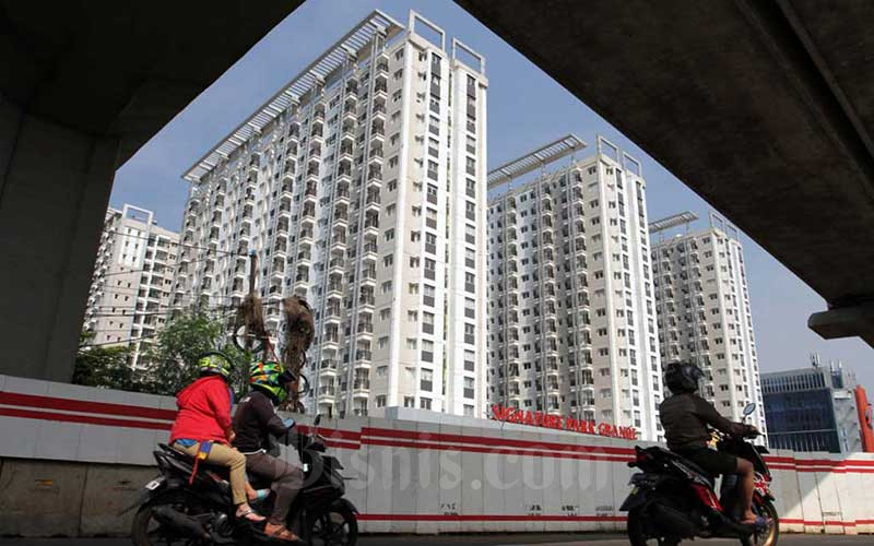 Kendaraan bermotor melintas di depan gedung apartemen di Jakarta, Jumat (29/5/2020). Bisnis - Dedi Gunawan