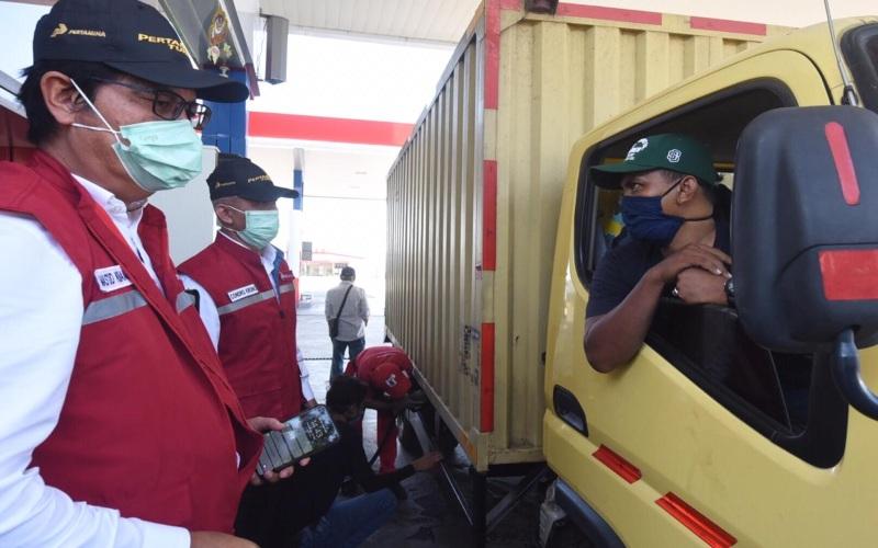 Komisaris Pertamina, Condro Kirono bersama Direktur Pemasaran Retail Pertamina, Mas'ud Khamid menyapa konsumen supir truk pada saat pemantauan kesiapan Satgas RAFICO 2020 yang dilaksanakan di SPBU KM 228, Cirebon, Jawa Barat, Rabu (20/5/2020). Istimewa -  Pertamina