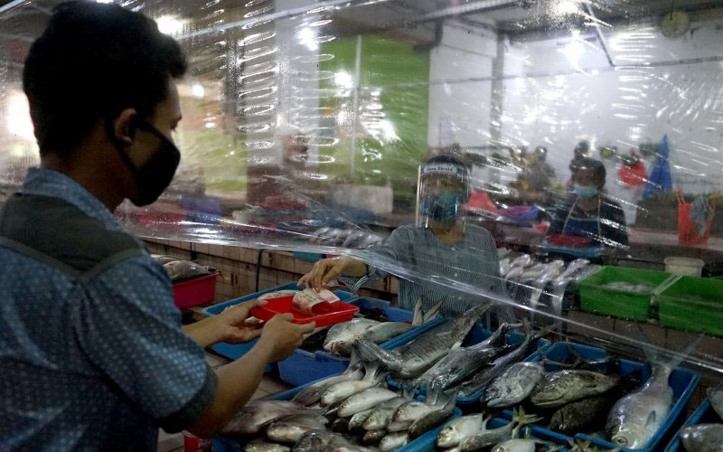 Salah satu contoh transaksi pembayaran antara penjual dan pembeli dengan menggunakan nampan di Pasar Genteng Baru, Kota Surabaya, Minggu 14 Juni 2020. Antara/Humas Pemkot Surabaya