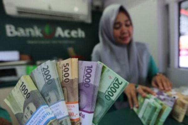 Seorang karyawati menghitung uang di salah satu kantor cabang Bank Aceh. - Antara/Irwansyah Putra