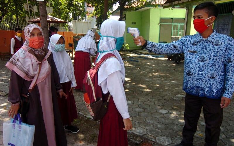 Seorang guru mengukur suhu tubuh calon siswa saat melakukan pendaftaran Penerimaan Peserta Didik Baru (PPDB) secara daring di SMPN 2 Tegal, Jawa Tengah, Rabu (17/6/2020). Mesipun pihak sekolah membuka pendaftaran PPDB secara daring di tengah pandemi COVID-19 yang dilaksanakan mulai 17 hingga 24 Juni 2020, tetapi sebagian pendaftar tetap datang ke sekolah karena masih bingung cara pendaftaran daring. - Antara/Oky Lukmansyah
