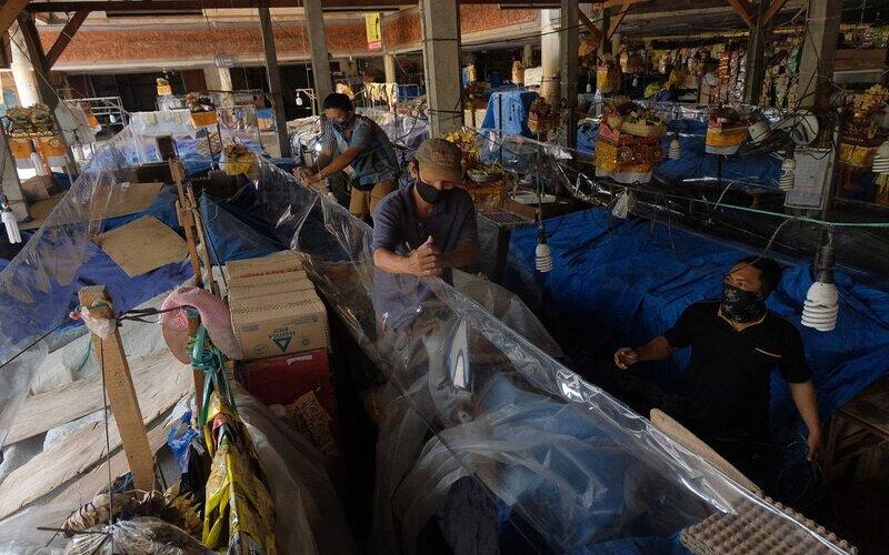 Petugas memasang plastik mika untuk menyekat lapak pedagang di pasar tradisional Cokroaminoto Denpasar, Bali, Senin (15/6/2020). Pemasang sekat plastik transparan tersebut sebagai upaya memutus rantai penyebaran Covid-19 secara transmisi lokal menyusul meningkatnya kasus itu di sejumlah pasar tradisional di Denpasar. - Antara/Nyoman Hendra Wibowo