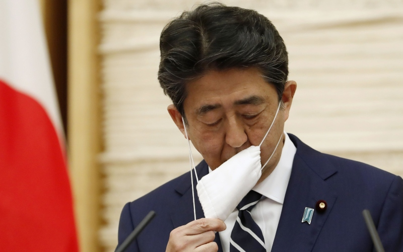 Perdana Menteri (PM) Jepang Shinzo Abe melepas maskernya sebelum berbicara dalam sebuah konferensi pers di Tokyo, Jepang, Senin (25/5/2020)./Bloomberg - Reuters/Kim Kyung/Hoon
