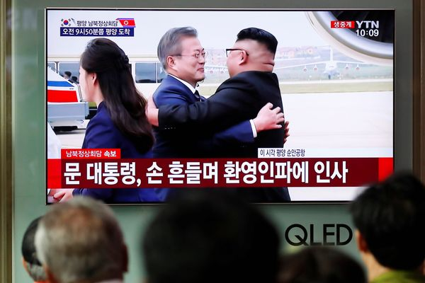 Warga Korea Selatan (Korsel) menonton tayangan televisi yang menunjukkan Presiden Korsel Moon Jae-in berpelukan dengan pemimpin tertinggi Korea Utara (Korut) Kim Jong Un ketika tiba di Pyongyang, Korut, Selasa (18/9). - Reuters/Kim Hong/Ji