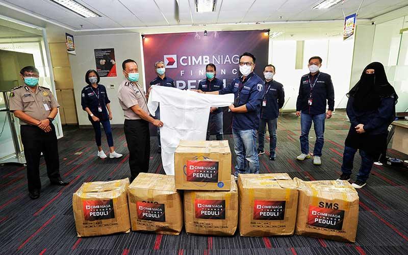 Presiden Direktur CIMB Niaga Finance Ristiawan Suherman (keempat kanan) menyerahkan bantuan kepada Perwakilan RS Polri Kombes Pol Drg. Saljiyana, DFM di Jakarta, Senin (13/4 - 2020). Bisnis