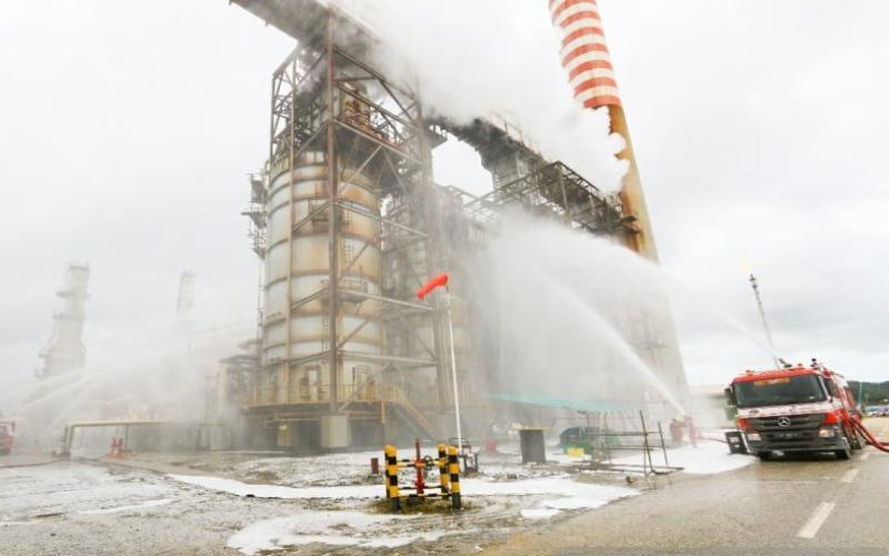 Regu pemadam kebakaran dari HSE Pertamina menyemprotkan air untuk mendinginkan unit yang terbakar, Jumat 19 - 6. Antara