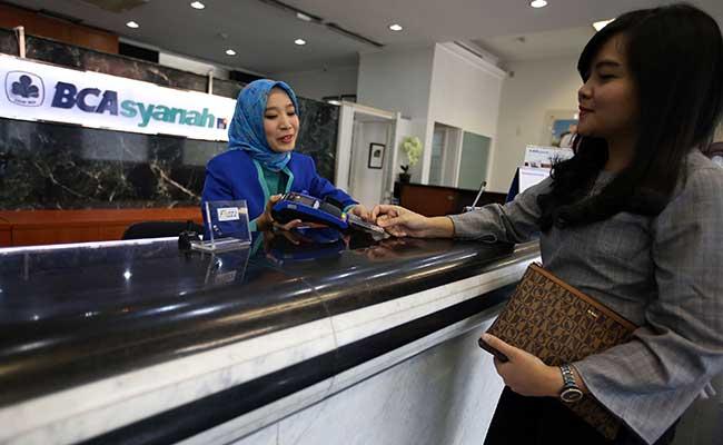 Karyawan melayani nasabah yang melakukan transaksi di kantor cabang Bank BCA Syariah di Jakarta. Bisnis - Abdullah Azzam