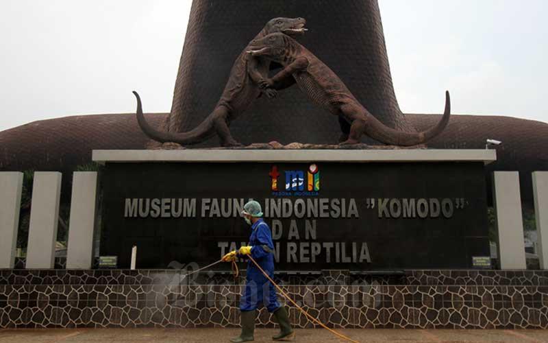 Petugas menyemprotkan cairan disinfektan di area Museum Fauna Indonesia Komodo dan Taman Reptilia di kawasan wisata Taman Mini Indonesia Indah (TMII), Jakarta, Selasa (18/3/2020). - Bisnis/Arief Hermawan P