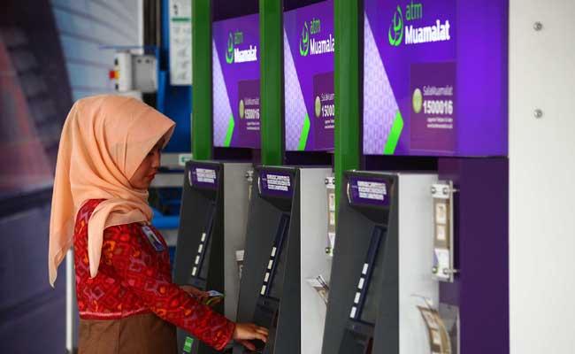Nasabah menggunakan mesin anjungan tunai mandiri bank Muamalat di Jakarta. Bisnis