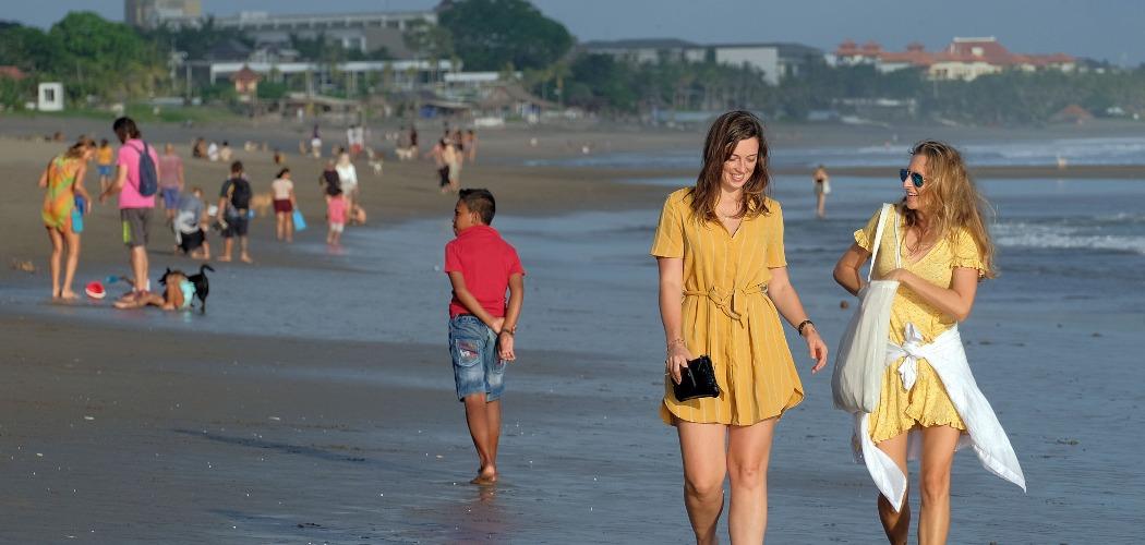 Wisatawan asing tanpa menggunakan masker berjalan di Pantai Berawa, Badung, Bali, Jumat (19/6/2020). Pemerintah Provinsi Bali berencana menerapkan tiga tahapan implementasi protokol kesehatan menyambut normal baru mulai 9 Juli 2020, di mana sektor pariwisata baru akan dibuka pada tahapan terakhir. - ANTARA FOTO/Nyoman Hendra Wibowo