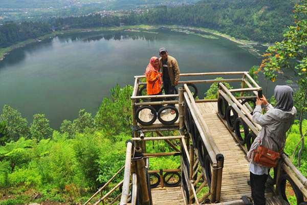 Wisatawan berfoto di atas anjungan bambu di lokasi wisata alam bukit Seroja, Desa Tlogo, Garung, Wonosobo, Jawa Tengah, Rabu (25/10). - ANTARA/Anis Efizudin