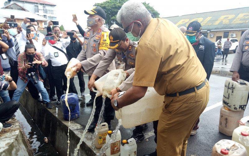 Kapolda Papua Irjen Paulus Waterpauw bersama Wakil Bupati Mimika Johannes Rettob menuangkan minuman keras lokal jenis sopi dari jerigen ke saluran drainase depan kantor pelayanan Polres Mimika, Senin 22 Juni 2020.  - Antara/varianus Supar\n