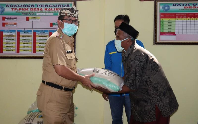 Bupati Cirebon, Imron Rosyadi menyerahkan bantuan beras kepada warga - Bisnis/Hakim Baihaqi