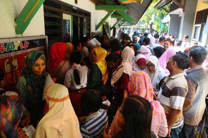 Sejumlah siswa dan orang tua murid antre untuk mengikuti seleksi Penerimaan Peserta Didik Baru (PPDB) jalur zonasi, di SMP 1 Kudus, Jawa Tengah, Rabu (19/6/2019). - ANTARA/Yusuf Nugroho