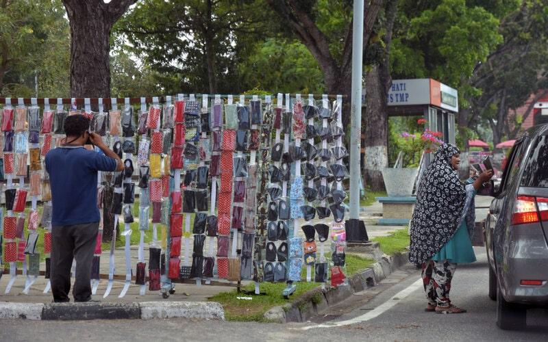 Sejumlah pedagang kaki lima menawarkan masker kain kepada pengguna jalan di Kota Pekanbaru, Riau, Selasa (7/4/2020). Penjual kaki lima menjual masker kain dan sarung tangan bermunculan di Kota Pekanbaru memanfaatkan langkanya masker saat wabah Covid-19 dengan harga jual berkisar Rp10.000 hingga Rp20.000 per helai. - Antara/FB Anggoro.\n