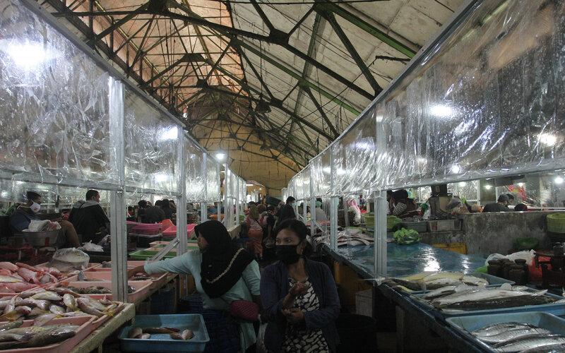 Warga beraktivitas di Pasar Ikan Pabean Surabaya, Jawa Timur, Senin (22/6/2020). Pasar tersebut menerapkan protokol pencegahan penularan Covid-19 seperti penyekat plastik di lapak pedagang, cuci tangan, jaga jarak dan kewajiban memakai masker bagi warga yang beraktivitas di pasar itu untuk memutus penularan Covid-19. - Antara/Didik Suhartono