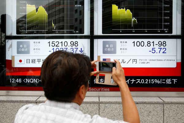 Seorang pejalan kaki memotret display indeks di Jepang. Reuters - Thomas Peter