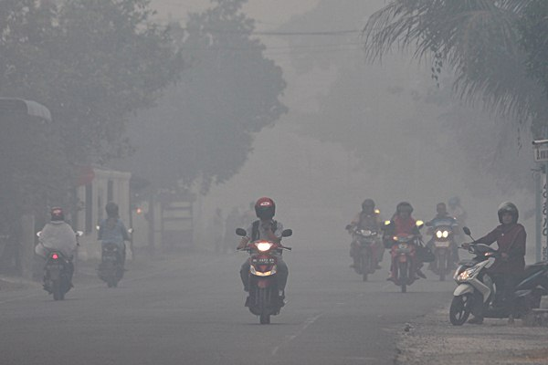 Warga berkendara menembus kabut asap di Jalan Nasional Banda Aceh, Tapak Tuan, Desa Suak Raya, Johan Pahlawan, Aceh Barat, Aceh, Kamis (27/7). - ANTARA/Syifa Yulinnas
