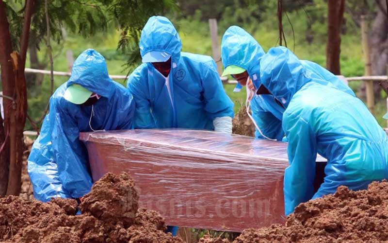 Petugas melakukan proses pemakaman jenazah pasien COVID-19 di TPU Tegal Alur, Jakarta, Kamis (9/4/2020). Bisnis - Eusebio Chrysnamurti