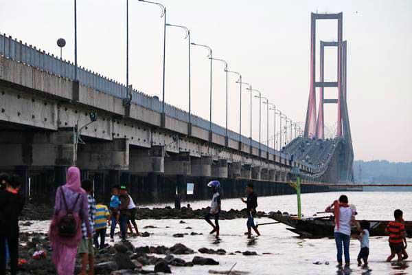 Warga menikmati suasana pantai di kawasan jembatan Suramadu, Surabaya, Jawa Timur, Senin (26/6). - Antara/Didik Suhartono
