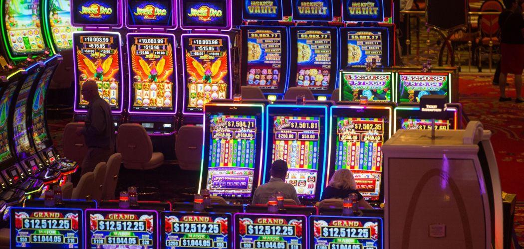 Para pemain menggunakan mesin judi di kasino Encore Boston Harbor, yang dikelola oleh Wynn Resorts Ltd., di Everett, Massachusetts, AS, Minggu (23/6/2019). - Bloomberg/Scott Eisen