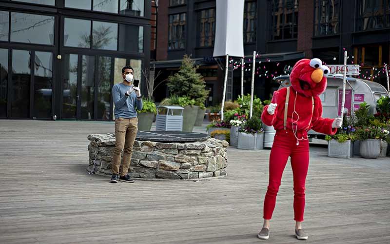 Warga yang menggunakan masker mengambil video seorang penari yang memakai kostum karakter Sesame Street Elmo di The Wharf, Washington, DC, Amerika Serikat, Selasa (7/4/2020). Amerika Serikat masih menjadi negara dengan kasus Covid-19 terbesar. Hingga Rabu (8/4/2020), kasus positif Covid-19 di Negeri Paman Sam itu telah mencapai 396.416 kasus. Bloomberg - Andrew Harrer
