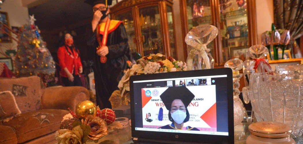 Hiero Lasut bersama ibunya bersiap mengikuti wisuda Universitas Sam Ratulangi secara daring dari rumahnya di Manado, Sulawesi Utara, Kamis (11/06/2020).Wisuda daring diselenggarakan dalam Sidang Terbuka Senat Universitas Sam Ratulangi periode IV yang diikuti 436 wisudawan dengan total peserta melalui aplikasi Zoom Meeting sebanyak 760 dan disiarkan secara langsung di situs Youtube. - ANTARA FOTO/Adwit B Pramono