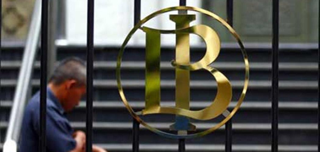seorang karyawan melintas dekat logo Bank Indonesia