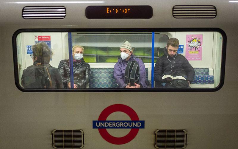Penumpang kereta bawah tanah di London mengenakan masker untuk menghindari penularan virus corona Covid-19. - Bloomberg